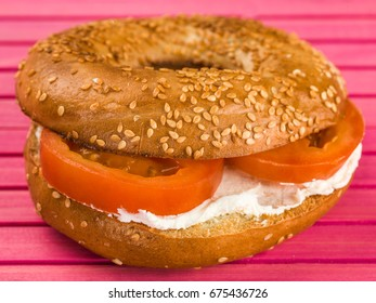 Cheese and Tomato Sesame Seed Bagel Against A Pink Background