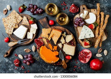 Cheese variety board or platter with cheese assortment, grapes, honey, nuts and wine in glasses. Black stone background. Top view, flat lay