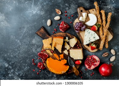 Cheese variety board or platter with cheese assortment, grapes, honey, nuts. Black stone background. Top view, flat lay