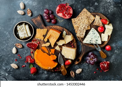 Cheese variety board or platter with cheese assortment, grapes, honey and nuts. Black stone background. Top view, flat lay
