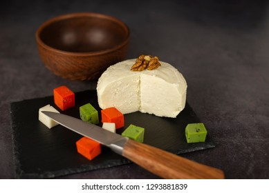 Cheese with walnut and multi-colored cubes of cheese on a black kitchen board
