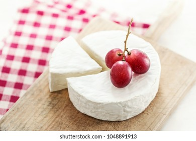 Cheese wheel with a piece of cheese on a wooden board with fruits and red checkered tablecloth. Camembert cheese close up.