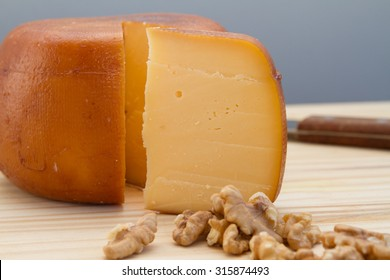 Cheese wheel and slice with nuts on a cutting board over a wooden table on natural environment.