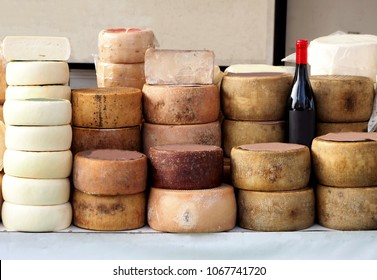 Cheese wheels of Pecorino and Sardinian ricotta in different stacks on a shelf of an outdoor market. A bottle of red wine Cannonau in the middle