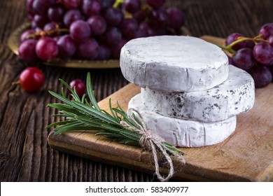 Cheese with white mold. Camembert or brie type. Grape and branch of rosemary. Healthy breakfast.