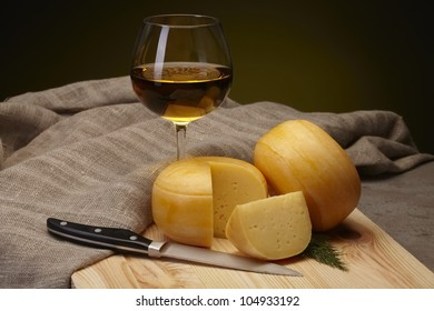 cheese with white wine on wooden table