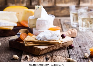 Cheese and wine party  table, perfect holiday appetizer on rustic wooden board, goat cheese with  crackers