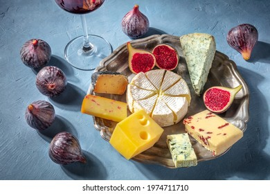 Cheese and wine. A cheese plate with Brie, blue cheese and other types, with fruit. A gourmet cheeseboard