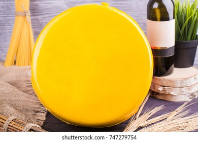 A cheese in a yellow film with a wine bottle