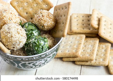 Cheeseballs with crackers on light wood background