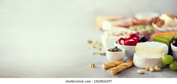 Cheeseboard. Assortment of hard, semi-soft and soft cheeses with olives, grissini bread sticks, capers on grey concrete backgound. Banner.