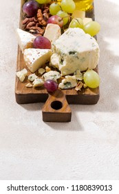 cheeseboard, fresh fruits, honey and white background, vertical, top view