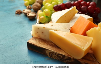 Cheeseboard, grape and nuts on blue textured background