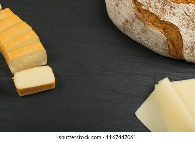 Cheeseboard with Sliced Limburger, Herve Cheese or Reblochon And Blue Gorgonzola, Roquefort or Stilton. Cheese Course with Mix of Yellow and Blue Cheeses Top View on Black Stone Plate Background