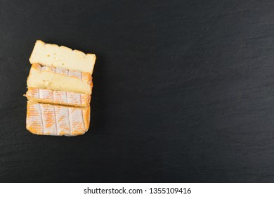 Cheeseboard with Sliced Yellow Limburger Cheese Top View. Herve or Reblochon cheeses, on Black Stone Plate Background