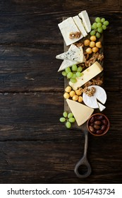 Cheeseboard with various cheeses, fruits and nuts. Dark wooden food background