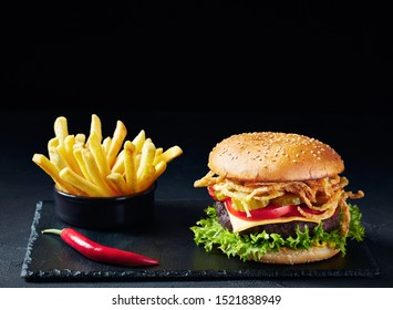 Cheeseburger with Beef Patty, cheddar cheese, crispy fried onions, lettuce, sliced tomatoes pickled cucumbers on a black stone board with french fries at the black background