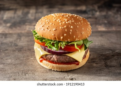 Cheeseburger with beef,tomato, lettuce and onion on wooden table