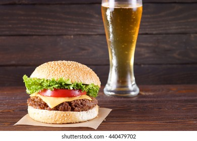 Cheeseburger with beer in background