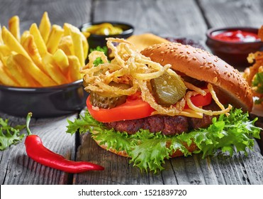 Cheeseburger with cheddar cheese, crispy fried onions, lettuce, sliced tomatoes, pickles on a rustic wooden table, close-up