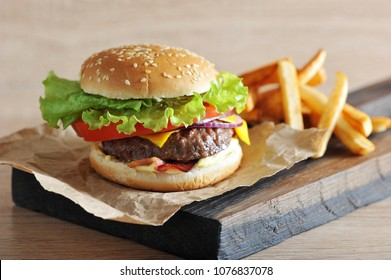 Cheeseburger from chopped beef cutlet with tomato, salad, bacon, sauce and red onion. Next to the cheeseburger is French fries. Light background. Close-up. Macro photography.