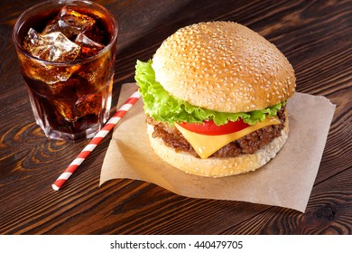 Cheeseburger and cola on texture boards. View from above.
