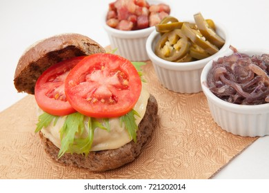 Cheeseburger with dark bread cheese tomato and aligned side servings of bacon onion cucumber