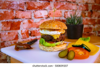 Cheeseburger with egg, pickles and jalapeno peppers