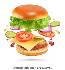 Cheeseburger. Flying burger with beef patty, cheese, pickles, tomato, onion and lettuce isolated on white background