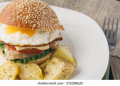 Cheeseburger with fried egg and potato wedges horizontal selective focus