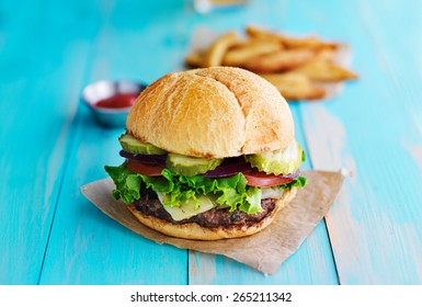 cheeseburger with fries and ketchup on rustic table top