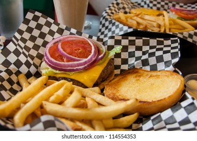 Cheeseburger and fries with lettuce, tomato, onion