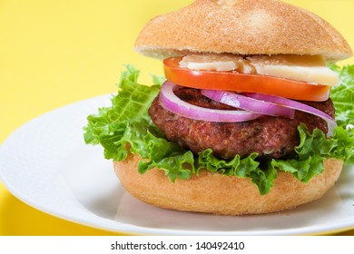 Cheeseburger isolated on yellow background