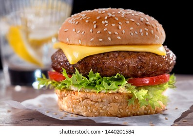 Cheeseburger with lettuce and tomato - accompanied by lemonade.
