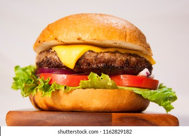 cheeseburger with lettuce, tomato, and onion on a brioche bun