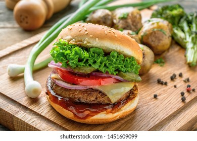 Cheeseburger made of meat burger, cheese, tomato, lettuce, onion and pickled cucumber with baked potato and broccoli.