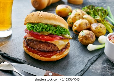 Cheeseburger made of meat burger, cheese, tomato, lettuce, onion and pickled cucumber with baked potato and broccoli served with glass of beer and sauce.