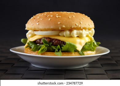 Cheeseburger with mayonnaise on dish with black background