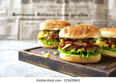 Cheeseburger with meat cutlet and pickled vegetable on a wooden cutting board on newspaper background.