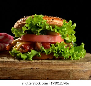 cheeseburger with minced meat, green lettuce and ketchup on a wooden brown kitchen board. Black background