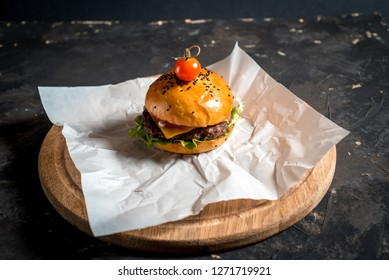 Cheeseburger on craft paper. Dried onions are scattered around the cheeseburger. Dark background. Close-up. Macro shooting.