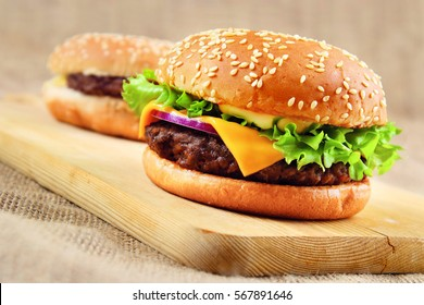 Cheeseburger on wooden cutboard.
