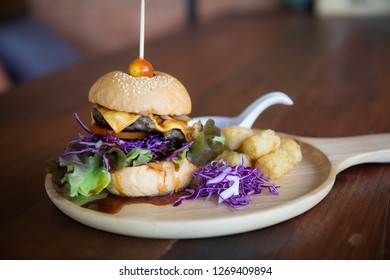 A cheeseburger platter with a side of tator tots on a wooden platter