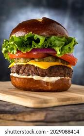 Cheeseburger with pretzel bun on a wooden board