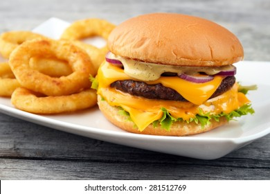 Cheeseburger served with deep fry onion rings on the white square dish and wooden board background