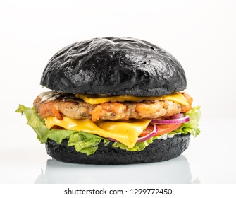 Cheeseburger with shrimps in a black bun on a white background with reflection. Black burger with seafood isolated on white.