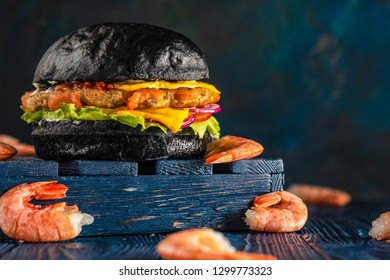 Cheeseburger with shrimps in a black bun on a wooden blue background. Black burger with seafood.