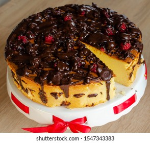 Cheesecake baked with melted chocolate. Garnished with raspberries. One piece cut out.
