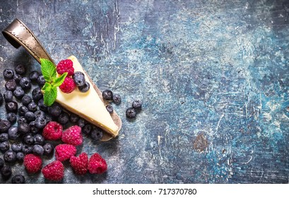 Cheesecake with berries on blue slate background. Selective focus. Place for text.