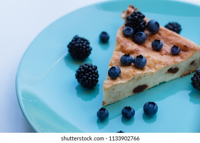 Cheesecake/ cake with berries on a blue/mint plate. Tasty breakfast/dessert